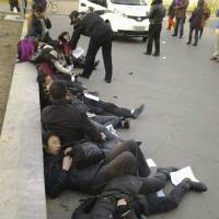 Desperation: Chinese from Wuhan province lie on the ground after drinking pesticide near a historic watchtower in the heart of Beijing to protest the demolition of their homes and the failures of a decades-old petitioning system for grievances. | AP