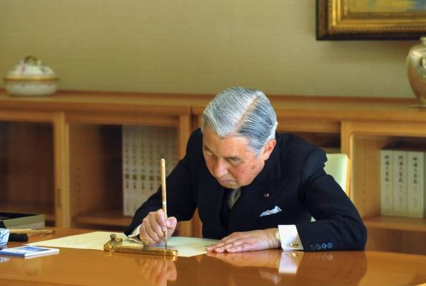 It's official: Emperor Akihito signs a government document Nov. 8 at the Imperial Palace.   IMPERIAL HOUSEHOLD AGENCY/KYODO
