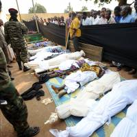 Intolerance aftermath: People stand near bodies found in a mosque and surrounding streets in Bangui, the capital of the Central African Republic, on Thursday after overnight violence. | AFP-JIJI