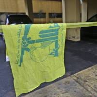 Crime scene: A Hezbollah flag hangs on yellow police tape sealing off the scene where Hassan al-Laqis, regarded as a senior commander for the Lebanese militant group Hezbollah, was gunned down outside his southern Beirut home Wednesday. | AP