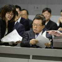 Facing the music: Tokyo Gov. Naoki Inose (center) looks at his papers as he prepares to respond to a committee from the Tokyo Metropolitan Assembly on Monday. | KYODO
