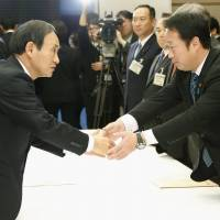 Let's make a deal: Chief Cabinet Secretary Yoshihide Suga (left) shakes hands with Iwakuni Mayor Yoshihiko Fukuda at the prime minister's office in Tokyo on Monday. | KYODO
