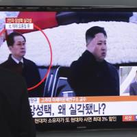 Now you see him: A man watches a TV news program Tuesday at a Seoul train station showing North Korean leader Kim Jong Un saluting as his uncle, Jang Song Thaek, looks on. Two South Korean lawmakers said Tuesday they were told by intelligence officials that Jang has been purged and two of his associates were executed last month. | AP