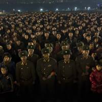 Paying their respects: North Koreans gather on the steps of Mansu Hill to lay flowers at the base of statues of the late leaders Kim Il Sung and Kim Jong Il in Pyongyang on Monday, the eve of the second anniversary of the death of Kim Jong Il. | AP