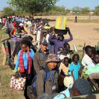 Caught in the middle: Civilians line up Wednesday outside the UNMISS compound in Bor, South Sudan, as fighting intensifies between forces loyal to fugitive former Vice President Riek Machar and President Salva Kiir. | AFP-JIJI