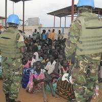 Peace eludes: United Nations soldiers stand guard as civilians gather at the compound of the U.N. Mission in the Republic of South Sudan (UNMISS), adjacent to Juba International Airport, to take refuge Wednesday amid spreading armed clashes among military factions. | AP