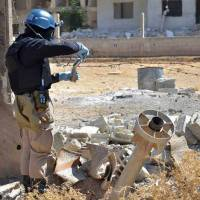 Evidence-gathering: A member of a U.N. inspection team examines what appears to be a Syrian chemical rocket outside Damascus in Ain Terma on Aug. 28. | AP