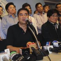 Exit plan: Democrat leader and former Prime Minister Abhisit Vejjajiva (center) speaks along with his party members during a press conference in Bangkok Sunday. The main opposition party announced it was resigning from parliament to protest what it called 'the illegitimacy' of the government. | AP