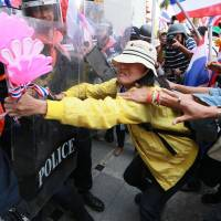Determined: Thai anti-government protesters (right) push through a line of riot police during a rally at the Department of Special Investigation on the outskirts of Bangkok on Monday. About 5,000 protesters took part in the rally and later stormed the DSI building. | AP