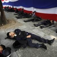 Breather: Police officers rest outside the prime minister's office compound, Government House, in Bangkok on Saturday. | AP