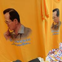 Hit pause: Anti-government protesters buy T-shirts with the face of King Bhumibol Adulyadej on Thursday to celebrate his 86th birthday at Democracy Monument in Bangkok. The revered Thai monarch urged the nation to work together for 'stability' in a speech the same day as days of violent anti-government protests paused. | AFP-JIJI