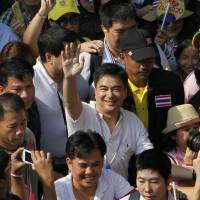 Center stage: Democrat Party leader and former Prime Minister Abhisit Vejjajiva (center) waves as he marches with anti-government protesters Dec. 9 in Bangkok. On Saturday, he announced the party will boycott a national election in February. | AP