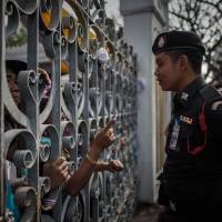 Accusatory: An anti-government demonstrator points his finger at a police officer through the gate of Government House in Bangkok on Thursday as political turmoil continued to rock the country. | AFP-JIJI