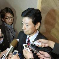 Seeking a balance: Japan's trade negotiator Yasutoshi Nishimura faces reporters after his meeting with U.S. Trade Representative Michael Froman in Singapore Sunday over the Trans-Pacific Partnership free trade talks. | KYODO