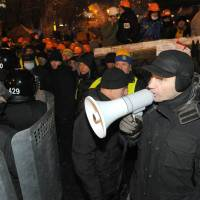 Loud and clear: Ukrainian opposition leader Vitali Klitschko speaks with a bullhorn to riot police on Independence Square in Kiev on Wednesday. Ukrainian security forces pulled out of the epicenter of mass protests after a nine-hour standoff with thousands of demonstrators. | AFP-JIJI