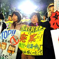 Women hold up signs calling for the abolition of the state secrets bill Friday in Tokyo's Hibiya Park, where 15,000 people gathered to protest the contentious legislation.    YOSHIAKI MIURA