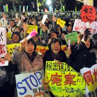 Protesters wave during a rally against the government's state secrets bill Friday in Hibiya Park in Tokyo.    YOSHIAKI MIURA
