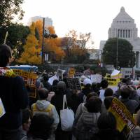 Protesters stare at the Diet building in Tokyo Friday during a rally against the government's secrecy protection bill, which could potentially make it easier to crack down on journalists and the public at large.  | SATOKO KAWASAKI