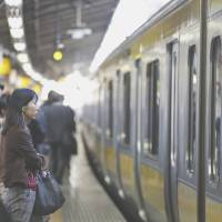 Mind the poverty gap: Commuters wait to board a train in Tokyo. Japan is plagued by underemployment — in terms of salaries, not workloads, with many 'part-timers' routinely putting in full-time shifts. | BLOOMBERG