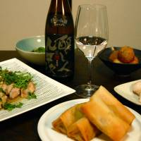 Hair of the dragon: Certain types of sake go great with Chinese food. This spread includes steamed chicken, spring rolls, stir-fried lettuce, shrimp dumplings, sesame balls and a bottle of Kamoshibito Kuheiji Kudan no Yamada junmai-ginjo nama sake. | MELINDA JOE