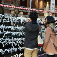 Visitors to Tokyo's Yushima Tenjin Shrine tie white paper ribbons bearing written fortunes on to wooden racks. The ribbons are called 'o-mikuji,' which literally translates as 'sacred lottery.' | YOSHIAKI MIURA