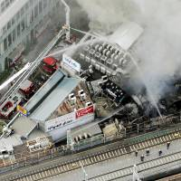 An aerial shot taken from a Kyodo News helicopter above Yurakucho Station shows firefighters at work around 9 a.m. Friday morning. The blaze reportedly started at around 6:30 a.m. and spread to three neighboring buildings.  | KYODO