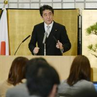 Abe tries to talk up pay, talk down Asia strains