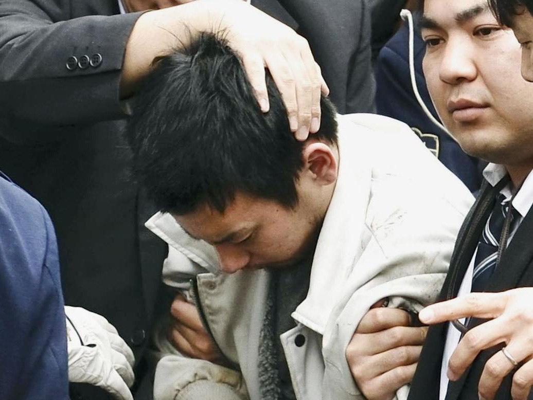 Yuta Sugimoto is taken by police officers to the Kawasaki branch of the Yokohama District Prosecutor's Office on Thursday after he was arrested in Yokohama.   KYODO