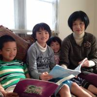 All in the family: Taichi (left), Mayu and Fuyu Sasada sit in their living room in December with their mother, Maho. | MAMI MARUKO