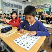 Fourth-graders play an alphabet-matching game last month at Minami Elementary School in Sayama, Saitama Prefecture. | YOSHIAKI MIURA