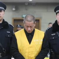 Day of reckoning: Guards present Lu Yueting, a former temporary worker at Tianyang Food in Hebei province, for sentencing at the Shijiazhuang Intermediate People's Court on Monday. The court sentenced Lu to life for lacing frozen dumplings with poison, causing 14 people in Japan and China to fall ill six years ago. | XINHUA/KYODO