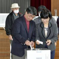 Yea or nay?: Incumbent Mayor Susumu Inamine (top) and his pro-base rival, Bunshin Suematsu, cast their votes on Sunday in Nago, Okinawa Prefecture. | KYODO