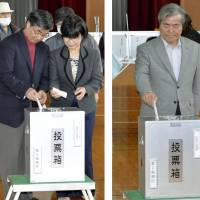 Yea or nay?: Incumbent Mayor Susumu Inamine (left) and his pro-base rival, Bunshin Suematsu, cast their votes on Sunday in Nago, Okinawa Prefecture. | KYODO