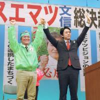 Vote for me!: Bunshin Suematsu (left), who is running in the Nago mayoral race, greets supporters Thursday.   KYODO
