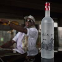 Drinking it up: A bottle of vodka with handmade illustrations of former NBA player Dennis Rodman with North Korean leader Kim Jong Un and Rodman's name in Korean sits on the roof of a car outside a Pyongyang hotel on Tuesday. | AP