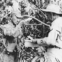 It's true: Former Imperial Japanese Army soldier Hiroo Onoda (left) accepts a pack of cigarettes from a member of a Japanese team sent to persuade him the war had ended, on Lubang Island in the Philippines in 1974. Onoda spent three decades in hiding on the island unaware that peace had broken out. | KYODO