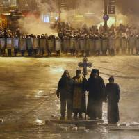 Holy smoke: Orthodox priests pray as they stand in no man's land between riot police and pro-EU activists in Kiev on Friday. | AP