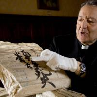 In black and white: The Rev. Cesare Pasini displays 18th-century Japanese manuscripts Tuesday at the Vatican Apostolic Library. | AP