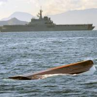 Adrift: A fishing boat floats capsized after colliding Wednesday with a Maritime Self-Defense Force ship (at rear) in the Seto Inland Sea off Hiroshima Prefecture.   CHUGOKU SHIMBUN/KYODO