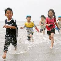 Not so fast: Children play on the beach in Zushi, Kanagawa Prefecture. The city is moving to crack down on rowdy and tattoo-wearing beachgoers. | KYODO