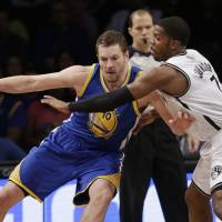 Net gain: Golden State's David Lee (left) tries to find a way past Brooklyn's Joe Johnson during the Nets' 102-98 win on Wednesday.   AP