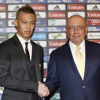Join the club: Keisuke Honda shakes hands with AC Milan CEO Adriano Galliani during his official presentation on Wednesday. | AP
