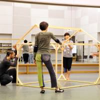 Shapes-shifting: Polka-dot-legged choreographer-director Shuji Onodera engages with members of the cast and a house-shaped framework during rehearsals for the upcoming run of his acclaimed non-dance work 'A Woman's House' being staged at the New National Theatre, Tokyo, this month. | YOSHIAKI MIURA
