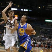 Streak continues: Golden State's Stephen Curry drives on Milwaukee's Luke Ridnour in the first half on Tuesday night. The Warriors beat the Bucks 101-80.   AP
