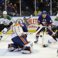 There for the taking: New York goalie Kevin Poulin blocks a shot from Dallas' Trevor Daley (second from right) on Monday night. | AP