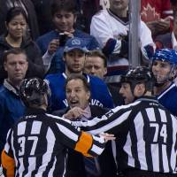 Fiery: Vancouver coach John Tortorella is restrained by referees as he screams at Calgary's bench on Saturday night. | AP