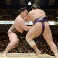 The grind begins: Yokozuna Hakuho (left) overpowers Tochiozan on the opening day of the New Year Grand Sumo Tournament in Tokyo on Sunday. | KYODO