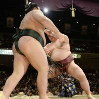 Back on track: Kisenosato (rear) takes on Chiyotairyu at the New Year Grand Sumo Tournament on Tuesday. | KYODO
