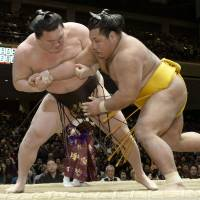 No change at the top: Yokozuna Hakuho (left) outmuscles Shohozan on Sunday, raising his record to 8-0 at the New Year Grand Sumo Tournament. | KYODO