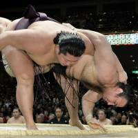 Muscular triumph: Endo overpowers Kotooshu on Friday at the New Year Grand Sumo Tournament, improving to 10-3.     KYODO